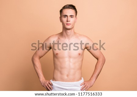 Portrait of handsome man with towel, naked torso, looking relax after bath, going to take shower, standing isolated on pastel beige background