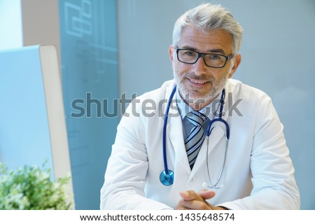Portrait of handsome mature doctor sitting at desk in modern office