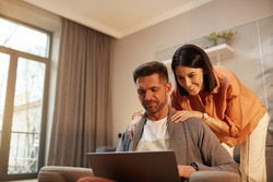 Portrait of handsome mature man using laptop while working from home with smiling wife embracing him, copy space