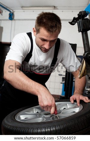Portrait of handsome mechanic fixing tire in car service