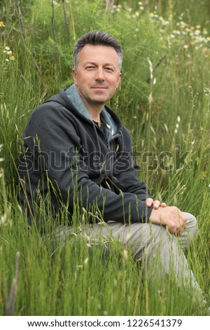 Portrait of handsome mid-adult man posing on summer meadowd looking at camera and happy smiling. #1226541379