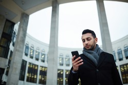 Portrait of handsome Middle-Eastern businessman using smartphone and reading text messages looking at screen of smartphone by modern city building