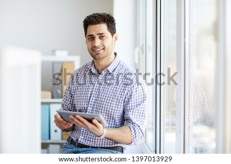 Portrait of handsome Middle-Eastern man looking at camera while posing by window holding tablet, copy space #1397013929