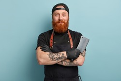 Portrait of handsome professional male butcher has arms crossed, holds metal sharp cleaver, wear black uniform, ready to start work, isolated over blue background. People and occupation concept