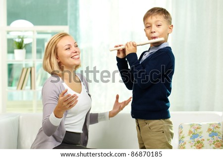 Portrait of handsome pupil playing the flute while happy tutor admiring his play