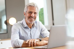 Portrait of handsome senior businessman working on laptop