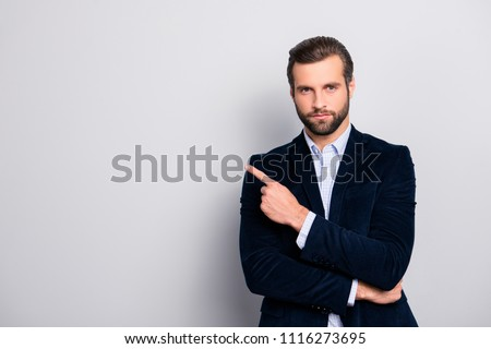 Portrait of handsome serious strict concentrated focused wealthy masculine virile elegant attractive banker with modern haircut pointing on empty blank space isolated on gray background copyspace #1116273695