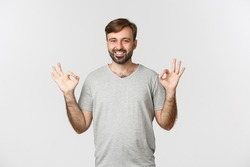 Portrait of handsome smiling man in casual grey t-shirt, showing okay sign in approval, agree to you, praising good choice, standing over white background