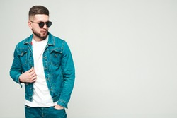 Portrait of handsome smiling stylish hipster lambersexual model.Man dressed in jacket and jeans clothes. Fashion male posing on grey background in studio in sunglasses