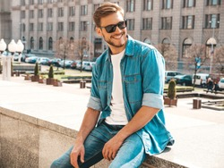 Portrait of handsome smiling stylish hipster lumbersexual businessman model. Man dressed in jeans jacket clothes. Fashion male posing on the street background in sunglasses