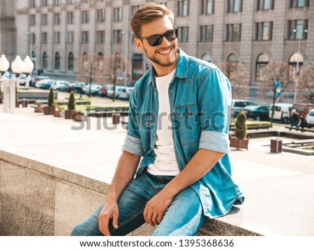 Portrait of handsome smiling stylish hipster lumbersexual businessman model. Man dressed in jeans jacket clothes. Fashion male posing on the street background in sunglasses Stock photo ©