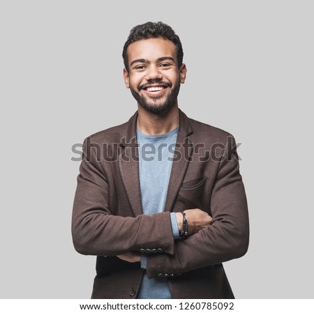Portrait of handsome smiling young man with folded arms. Laughing joyful cheerful men with crossed hands studio shot. Isolated on gray background #1260785092