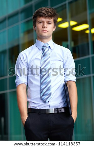 Portrait of handsome standing attractive businessman with briefcase, background