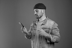 Portrait of handsome stylish man holding his modern smartphone while reading messages attentively and keeping his spectacles in hand