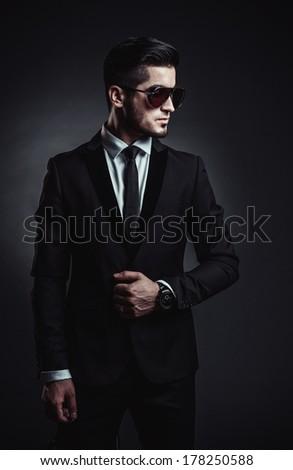 Portrait of handsome stylish man in elegant black suit and sunglasses
