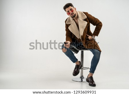 Portrait of handsome stylish model male in coat and sunglasses sitting on bar stool in studio, holding bottle in hand looking at the camera, gray background