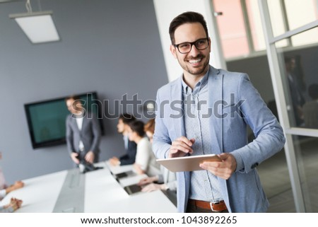 Portrait of handsome successful businessman holding tablet #1043892265