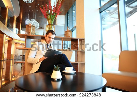 Portrait of handsome successful man drink coffee and look to the digital tablet screen sitting in coffee shop, business man having breakfast at hotel lobby