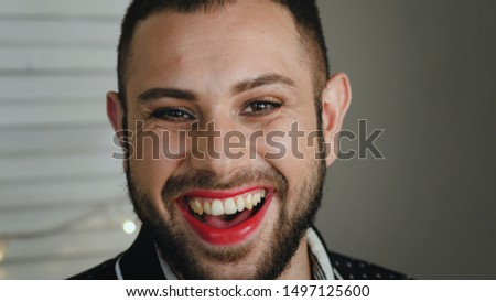 Portrait Of Handsome Young Bearded Man With Cosmetics On Face Genuinely Laughs. Metrosexual Or Gay Man With Red Lipstick Laughing At Camera #1497125600