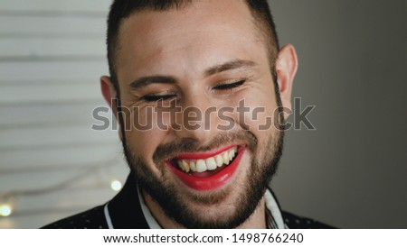 Portrait Of Handsome Young Bearded Man With Cosmetics On Face Genuinely Laughs With Eyes Closed. Metrosexual Or Gay Man With Red Lipstick Laughing At Camera #1498766240