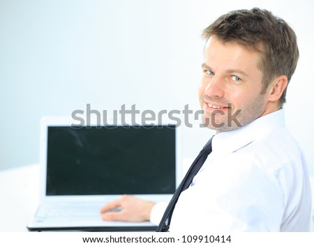 Portrait of handsome young business man and laptop