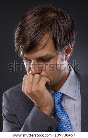 portrait of handsome young business man thinking against a gray background