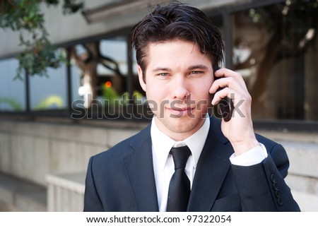 Portrait of handsome, young business man using cell phone