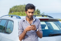Portrait of handsome young business man using texting on mobile phone next to his car, calling 911 after an accident while standing outdoors green bush tree and blue sea and sky on background