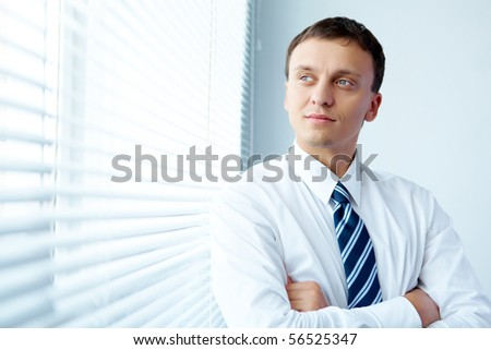 Portrait of handsome young businessman by the window