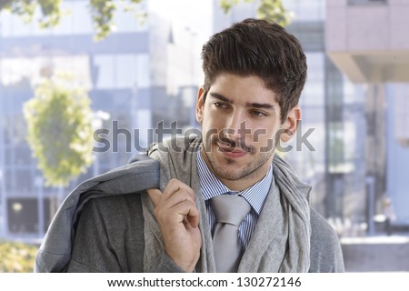 Portrait of handsome young businessman smiling.