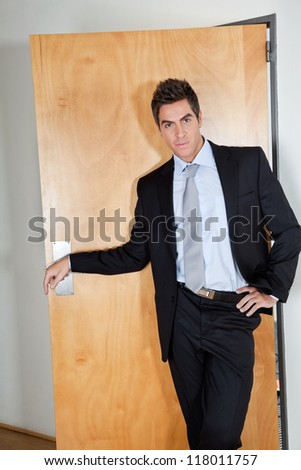 Portrait of handsome young businessman standing with hand on hip in office