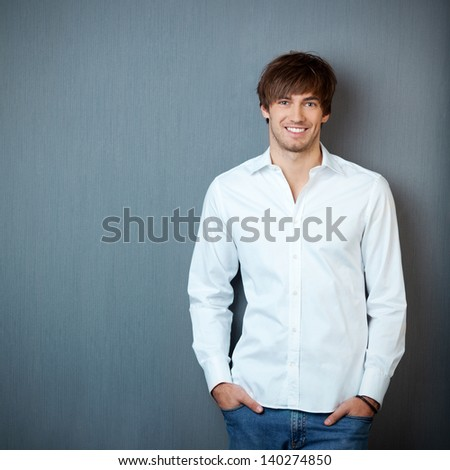 Portrait of handsome young businessman standing with hands in pockets against blue wall