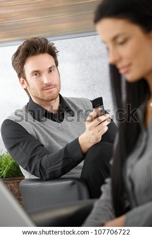 Portrait of handsome young businessman with mobile phone.