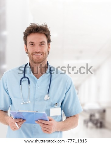 Portrait of handsome young doctor on hospital corridor looking at camera smiling