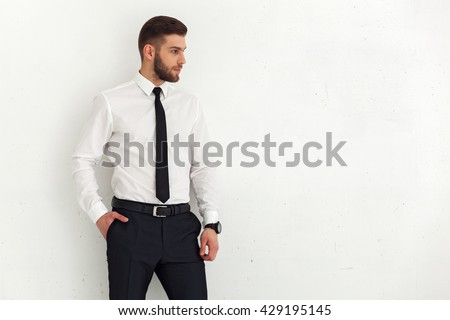 Portrait of handsome young guy standing against white wall. #429195145