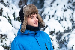 Portrait of handsome young happy man in winter clothes with hat with ear flaps. He is smiling and enjoying good winter day and cold snowy weather