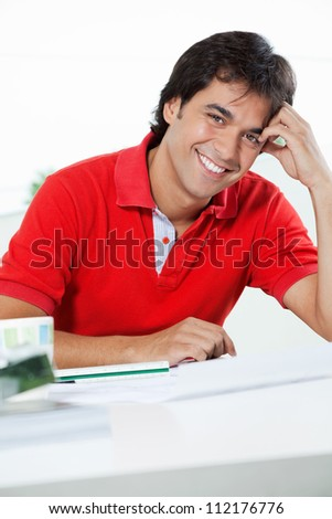 Portrait of handsome young male architect in casual t-shirt smiling while sitting at desk