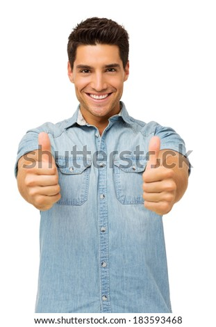 Portrait of handsome young man gesturing thumbs up while standing against white background. Vertical shot.