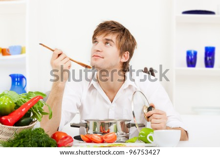 portrait of handsome young man hold spoon taste, pan with ready meal, soup, boiler in the kitchen, happy smile, think looking up