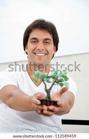 Portrait of handsome young man holding a small artificial plant