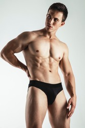 Portrait of handsome young man in black underwear posing over gray background. Perfect hair & skin. Close up. Studio shot