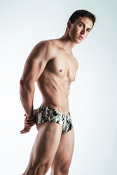 Portrait of handsome young man in camouflage printed underwear posing over white background. Perfect hair & skin. Studio shot