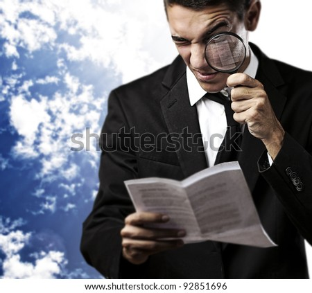 portrait of handsome young man looking a contract through a magnifying glass against a blue sky background