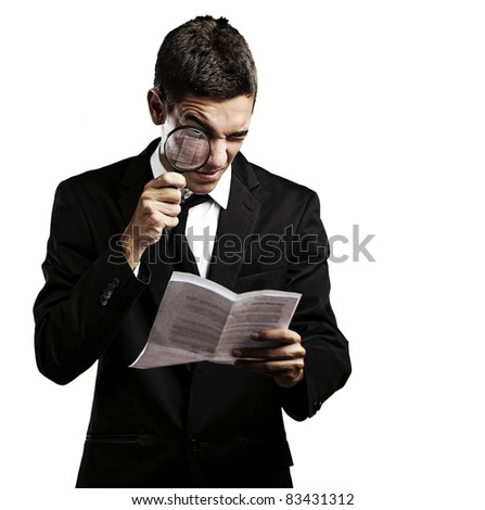 portrait of handsome young man looking a contract through against a white background