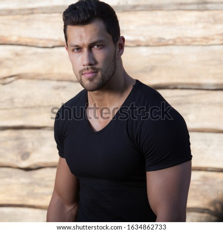 Portrait of handsome young man on wooden background.
