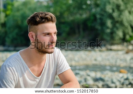 Portrait of handsome young man outdoors in nature, looking to a side