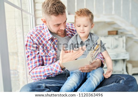Portrait of handsome young man playing with his cute son while sitting on window together and reading card for Fathers day - Shutterstock ID 1120363496