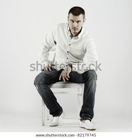 Portrait of handsome young man sitting on a chair