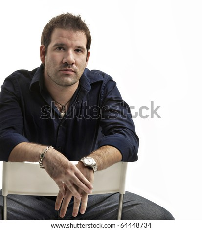 Portrait of handsome young man sitting on a chair isolated against white background - stock photo
