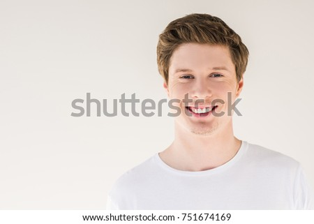 portrait of handsome young man smiling at camera isolated on grey